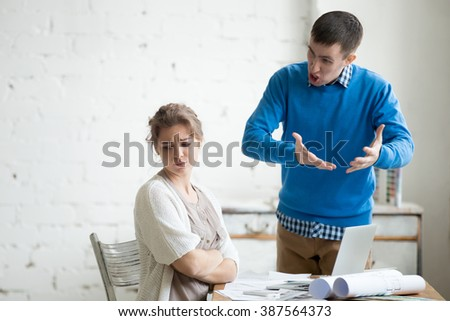 Portrait of two coworkers arguing at work. Staff in the middle of argument at modern office. Young furious man yelling at annoyed stressed woman with crossed arms. Negative human emotions Royalty-Free Stock Photo #387564373