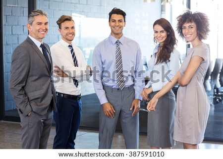 Portrait of confident business team standing in office #387591010