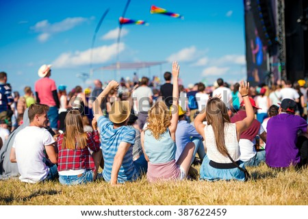 Teenagers, summer music festival, sitting in front of stage Royalty-Free Stock Photo #387622459