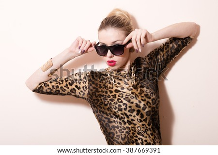 Picture of seductive blond lady in sunglasses wearing leopard print dress and sunglasses over white background