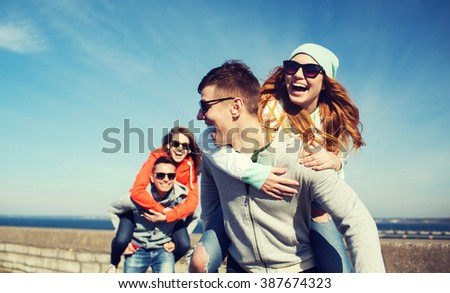 friendship, leisure and people concept - group of happy teenage friends in sunglasses having fun outdoors #387674323