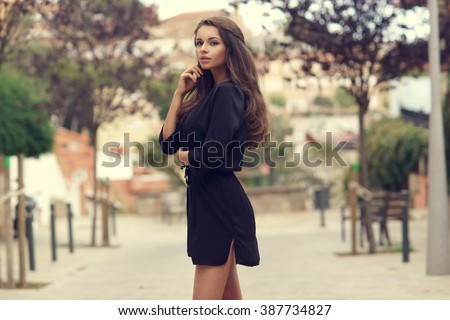 Young beautiful stylish girl in black summer dress walking and posing between trees at alley                                Royalty-Free Stock Photo #387734827