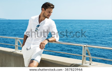 Handsome man wearing white clothes posing in sea scenery #387823966