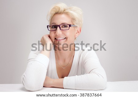 Portrait of beautiful blonde woman with short hairstyle. Woman in eyeglasses. Looking at camera, smiling. Studio shot. #387837664