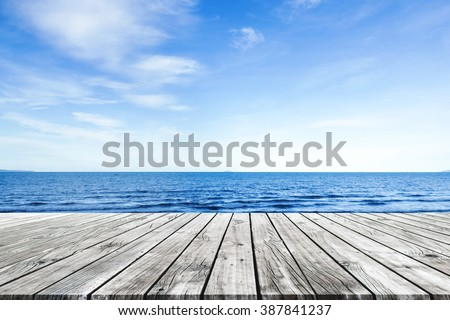 Wooden pier with blue sea and sky background Royalty-Free Stock Photo #387841237