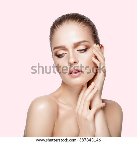 Studio portrait of young beautiful model with hands near her face on pink background. Perfect fresh clean skin. professional makeup. Brunette hair. Hands touching her face. Not isolated #387845146