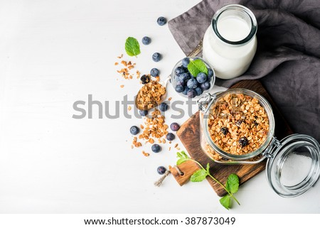 Healthy breakfast ingredients. Homemade granola in open glass jar, milk or yogurt bottle, blueberries and mint on white wooden background, top view, copy space #387873049