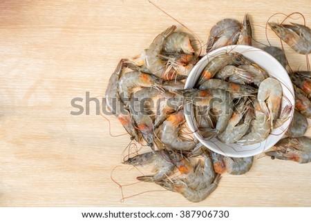 group of fresh shrimp in the white bowl on wooden #387906730