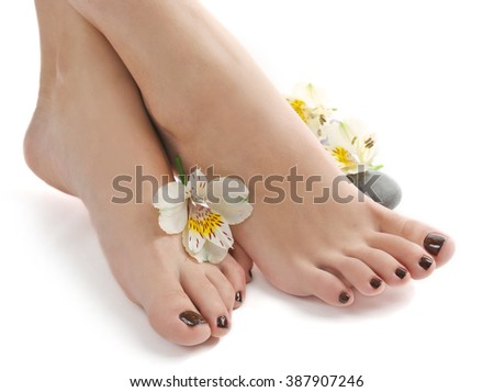 Manicured female feet with spa stones and flowers isolated on white #387907246