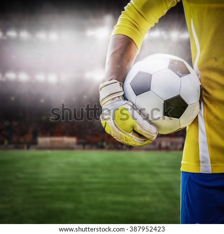 close up goalkeeper holding soccer ball in the stadium  #387952423