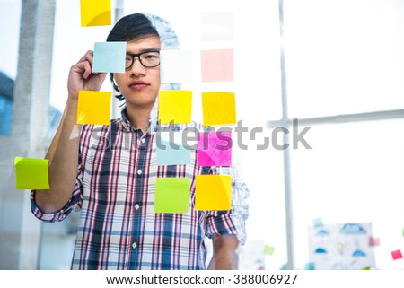 Creative businessman writing on sticky notes in office #388006927