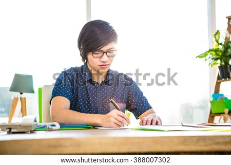 Focused hipster businessman writing in office #388007302