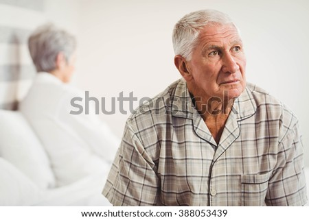 Upset senior man sitting on the opposite ends of the bed after a fight #388053439