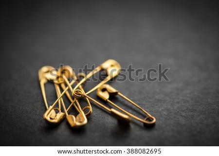Safety pin on a dark background. Selective focus. Royalty-Free Stock Photo #388082695