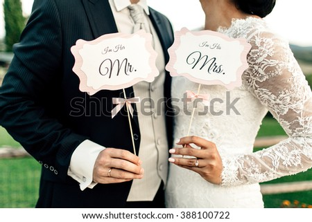 Happy newlyweds holding decorative plates in hands on the ceremony