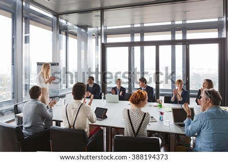 Business people clapping hands after successful meeting  in modern office. #388194373