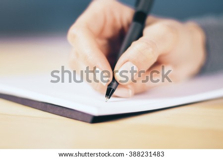 Girl hand with pen and notebook on wooden table, close up #388231483