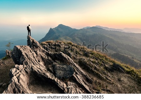 businessman hike on the peak of rocks mountain at sunset, success,winner, leader concept Royalty-Free Stock Photo #388236685
