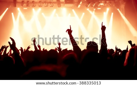 silhouettes of concert crowd in front of bright stage lights #388335013