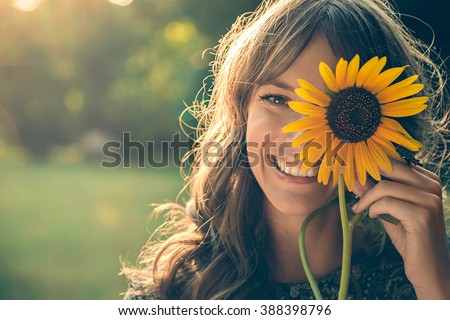 Girl in park smiling and covering face with sunflower Royalty-Free Stock Photo #388398796