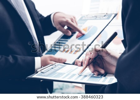 Business people discussing the charts and graphs showing the results of their successful teamwork Royalty-Free Stock Photo #388460323