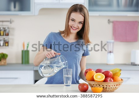 Young woman pouring water from jug into glass in the kitchen #388587295