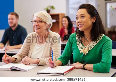 Two women sharing a desk at an adult education class look up #388591426