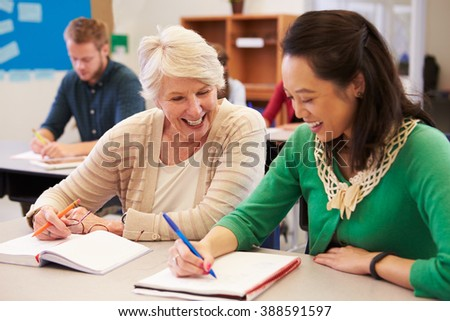 Teacher and student sit together at an adult education class #388591597