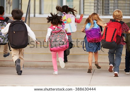 Elementary school kids running into school, back view Royalty-Free Stock Photo #388630444