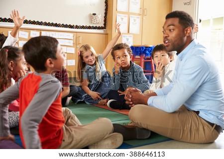 Elementary school kids and teacher sit cross legged on floor Royalty-Free Stock Photo #388646113