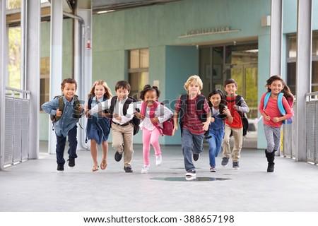 Group of elementary school kids running in a school corridor #388657198