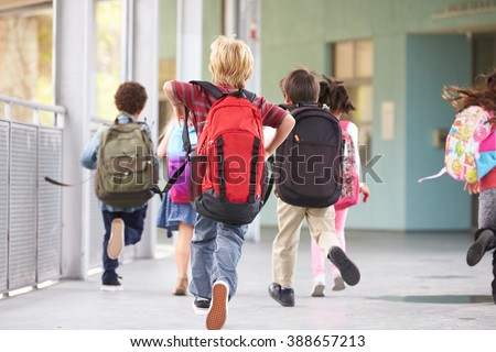 Group of elementary school kids running at school, back view Royalty-Free Stock Photo #388657213