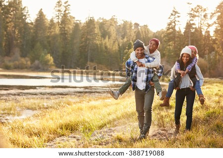 Parents Giving Children Piggyback Ride On Walk By Lake Royalty-Free Stock Photo #388719088