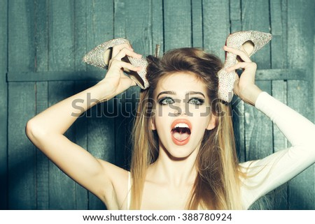 Portrait of emotional crazy glamour fashion young girl with long beautiful hair holding shoes in raised hands near face on wooden background, horizontal picture