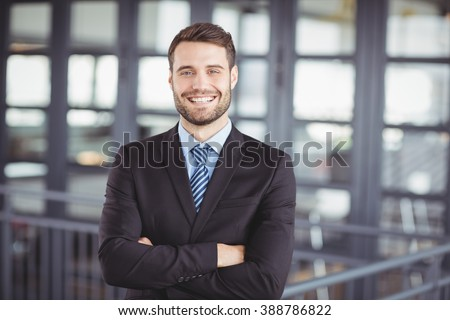 Portrait of happy businessman with arms crossed standing in office Royalty-Free Stock Photo #388786822