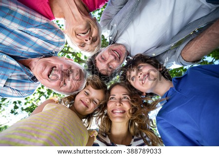 Smiling family with their heads in a circle in the garden #388789033