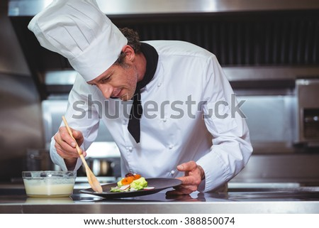 Chef putting sauce on a dish in a commercial kitchen #388850074