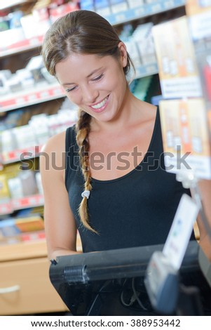 Lady working the till in a tobacconists Royalty-Free Stock Photo #388953442