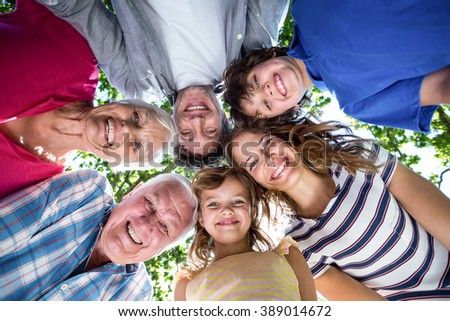 Smiling family with their heads in a circle in the garden #389014672