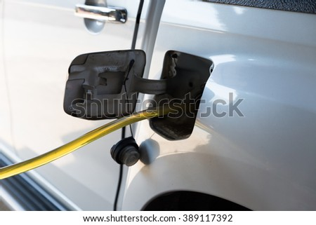 people using traditional way to fill up the gas tank with rubber tube #389117392