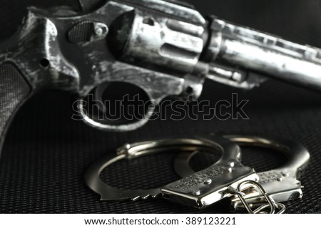 The chrome metal handcuffed and plastic toy gun represent the crime fraud and punishment equipment concept related idea. #389123221