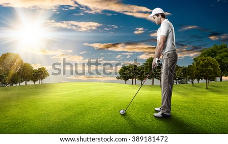 Golf Player in a white shirt taking a swing, on a golf course. #389181472