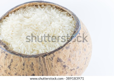 Rice in a coconut shell on a white background. #389183971