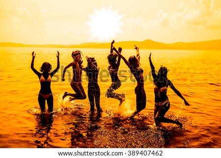 Silhouette of young group of people jumping in ocean at sunset. Team of adult girl jump in water on summer beach against blue sky with clouds Water splash Hair fly in air. Empty space for inscription #389407462