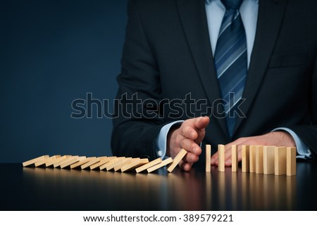 Businessman stop domino effect. Risk management and insurance concept, leadership has solution for problem.  Royalty-Free Stock Photo #389579221