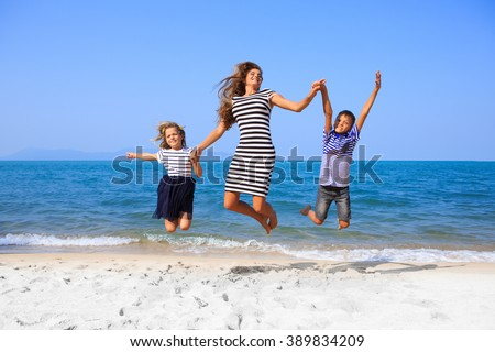 Happy family mother, daughter and son having fun on beach sand. Parent mom and children kids with toys at sea. Summer vacation holidays relax and happiness. #389834209