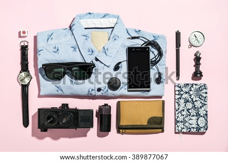 Overhead view of men's casual outfits on gray paper board background, Essential vacation items