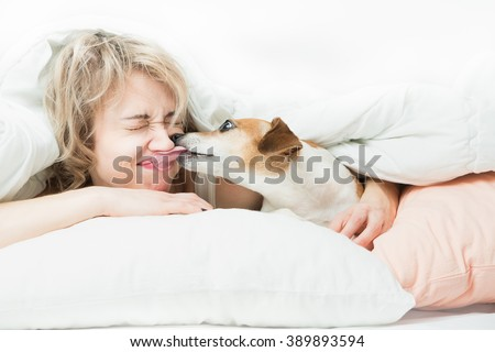 Blonde beautiful Woman and dog playfully indulge in fun on the bed. Dog bites the girl's nose. Happy time with pets