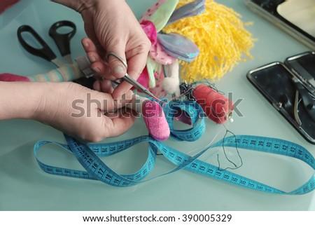 Repair of a damaged doll, concept of craftsmanship, closeup studio shot with selective focus #390005329