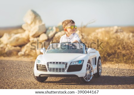 Funny boy car driver with the steering wheel. year-old boy in a white shirt in a red toy car in the street. Little boy driving big toy car and having fun, outdoors. Young kid portrait with toy car Royalty-Free Stock Photo #390044167